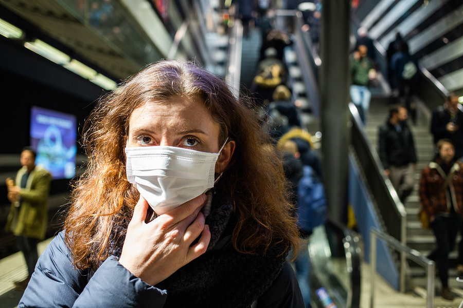 woman wearing surgical mask in crowd coronavirus